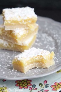 The Best Lemon Bars Recipe in the World, featured by top US food blog, Among the Young: image of lemon bars on a plate | Almond Roca by popular Utah lifestyle blog, Among the Young: image of lemon bars on a grey plate.