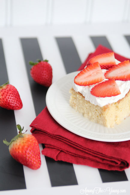 The most delicious tres leches cake featured by top Utah Foodie blog, Among the Young: image of tres leches cake and strawberries | Easy Tres Leches Recipe by popular Utah lifestyle blog, Among the Young: Pinterest image of Tres Leches cake.