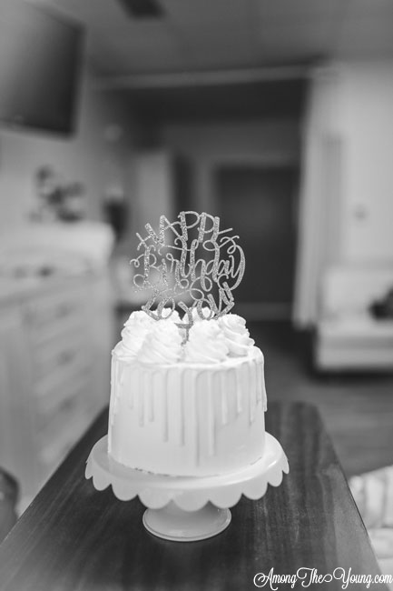 Baby girl birth story by top Utah lifestyle blog, Among the Young: image of cake | Birth Story by popular Utah motherhood blog, Among the Young: black and white image of a layer cake with a Happy Birthday cake topper.