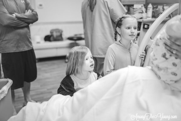 Baby girl birth story by top Utah lifestyle blog, Among the Young: image of girls seeing the baby | Birth Story by popular Utah motherhood blog, Among the Young: black and white image of two young girls looking at their newborn sister.