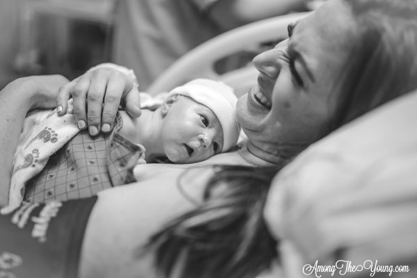 Baby girl birth story by top Utah lifestyle blog, Among the Young: image of mom laughing and holding the baby | Birth Story by popular Utah motherhood blog, Among the Young: black and white image of a woman laying in a hospital bed while holding her new born baby on her chest.