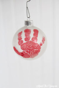 The cutest DIY handprint ornament featured by top Utah craft blog, Among the Young: image of red hand close up