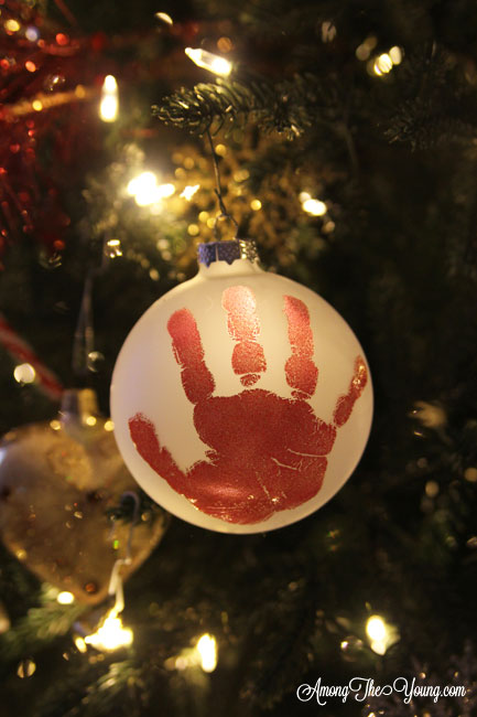The cutest DIY handprint ornament featured by top Utah craft blog, Among the Young: image of red handprint ornament in tree | How to make the cutest DIY handprint ornament by popular Utah life and style blog, Among the Young: image of a DIY handprint ornament.
