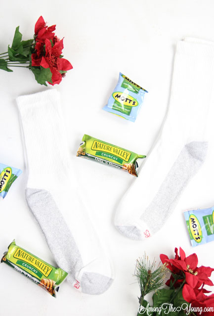 How to give back to the community this Christmas season featured by top Utah lifestyle blog, Among the Young: image of poinsettias and socks |Give Back by popular Utah lifestyle blog, Among the Young: image of a socks, granola bars, and fruit snacks.