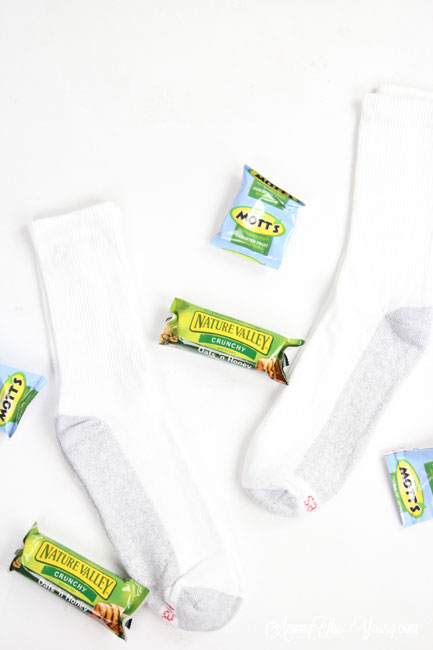 How to give back to the community this Christmas season featured by top Utah lifestyle blog, Among the Young: image of socks and granola bars |Give Back by popular Utah lifestyle blog, Among the Young: image of a socks, granola bars, and fruit snacks.
