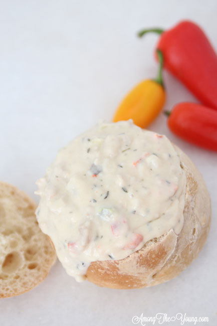 The best Disneyland Clam chowder featured by top Utah Foodie blog, Among the Young: image of clam chowder dripping out of bread bowl | Copycat Recipes: Disneyland Clam Chowder Recipe by popular Utah food blog, Among the Young: image of copycat Disneyland clam chowder in a bread bowl.