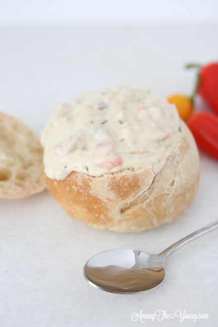The best Disneyland Clam chowder recipe featured by top Utah Foodie blog, Among the Young: image of clam chowder with a spoon | Copycat Recipes: Disneyland Clam Chowder Recipe by popular Utah food blog, Among the Young: image of copycat Disneyland clam chowder in a bread bowl.
