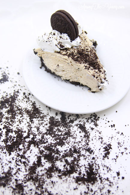 The Best easy Peanut Butter Pie by top Utah Foodie blog, Among the Young: image of messy oreos and slice of pie | Easy Peanut Butter Pie Recipe by popular Utah food blog, Among the Young: a slice of peanut butter pie on white plate that's surrounded by crushed Oreos.