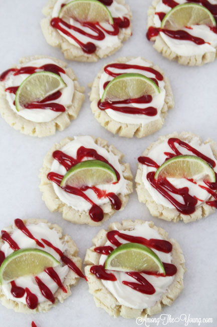 The most amazing raspberry lime sugar cookies featured by top Utah Foodie blog Among the Young: image of cookies scattered | Key Lime Raspberry Sugar Cookies by popular Utah food blog, Among the Young: image of key lime raspberry sugar cookies.
